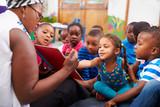 Fototapety Teacher reading a book with a class of preschool children
