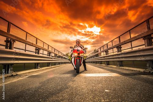 Moto da strada pronta alla partenza sotto un cielo rosso al tramonto Poster