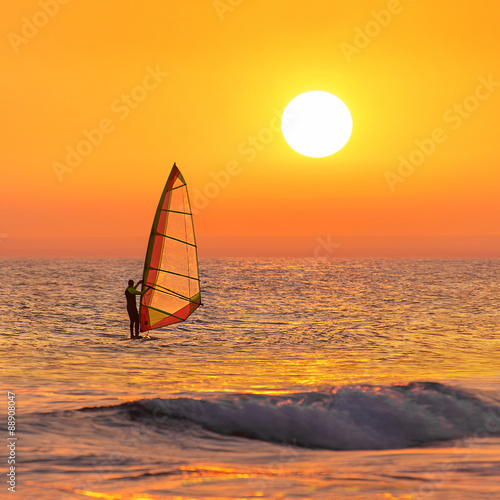 fototapeta na ścianę Windsurfer silhouette at sea sunset. Summertime watersports