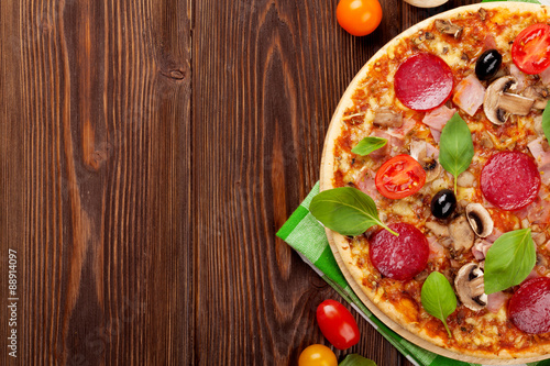 Italian pizza with pepperoni, tomatoes, olives and basil