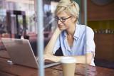 Fototapety Businesswoman Working On Laptop In Coffee Shop
