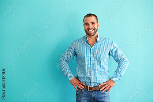 fototapeta na ścianę Happy man in front of turquoise wall