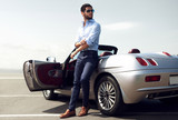 Fototapety Handsome man near the car. Luxury life.