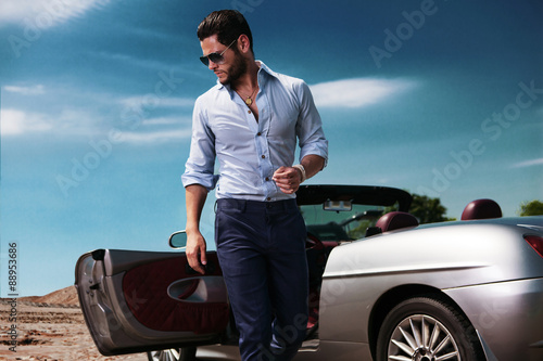 Handsome man near the car. Luxury life. Poster