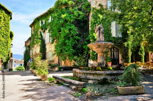 Leafy town square with fountain in a picturesque village in Provence, France Poster