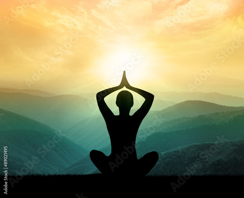 Yoga and meditation. Silhouette of man in moontains.