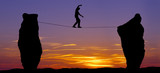 Silhouette of a man walking on the tightrope - 89084207