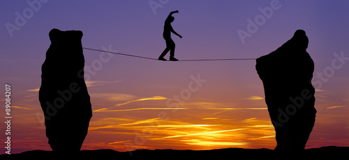 Silhouette of a man walking on the tightrope
