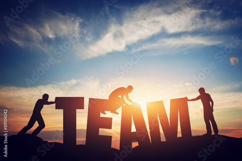 People connect letters to compose the team word. Teamwork concept