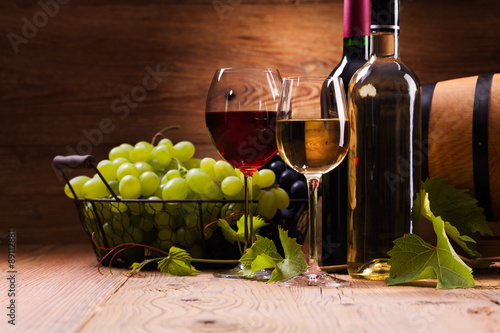 Fototapeta Glasses of red and white wine, served with grapes