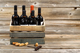 Bottles of red wine in wooden crate on rustic wooden boards