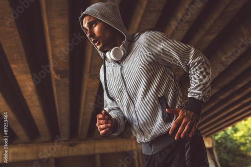 Fototapeta Jogger running in city environment.He wearing headphones around neck.