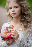 Closeup  lifestyle portrait little bridesmaid  with bouquet  Beautiful child in  Park