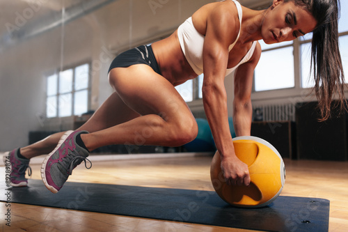 Poster, Tablou Muscular woman doing intense core workout in gym