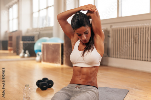 obraz lub plakat Fitness woman doing stretching exercise at gym