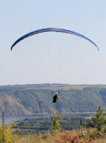 Deurstickers Ballon Paraglider flying on hills and river background. Back view