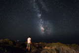 Fototapety Lone man looks with amazement at the night sky with the Milky Way - horizzontal version