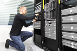 It consultant replaces harddrive in datacenter storage poster