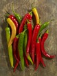 Fresh chillies (red, yellow, green) on wooden background - 89473423