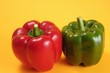 One red and one green pepper against a yellow background - 89479619