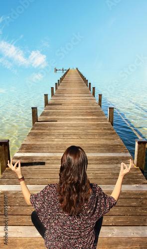 junge Frau meditiert am Badesteg, türkisblaues Wasser und Himme