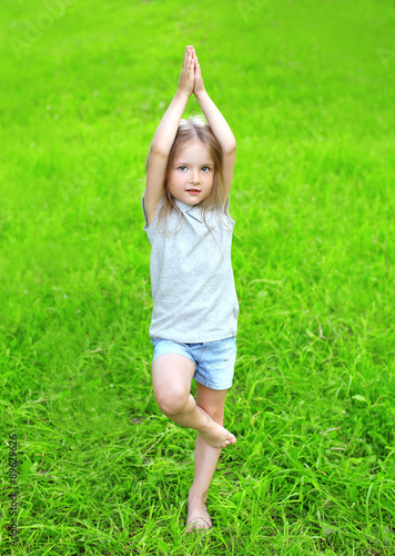 canvas print picture Little girl child on the grass does yoga exercise outdoors in su