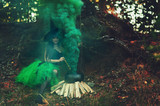 woman witch in the forest preparing a potion in a cauldron