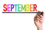 Hand with marker writing the word September