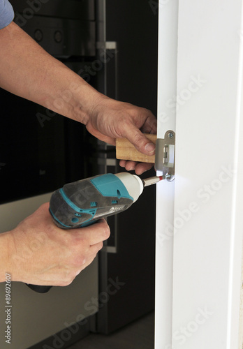 Carpenter screwing the bolt of a door Poster