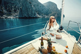 Fototapety Luxury vacation at sea on yacht. Beautiful woman with wine, fruit and mobile phone on boat