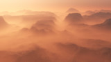 Mountain range glowing in the mist at sunrise. Aerial view.