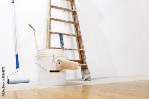 Poster painter wall concept, ladder, bucket, roll paint on the floor