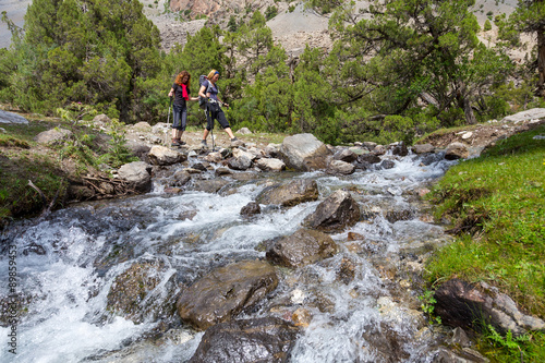 Two hikers crossing fast flowing river People going across mountain creek with f Poster