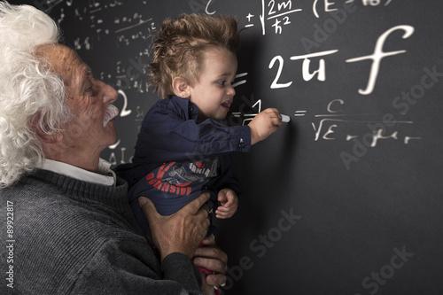 Nonno scienziato con nipotino in braccio che scrive alla lavagna плакат