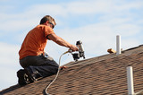 Building contractor putting the asphalt roofing on a large commercial apartment building. - 89963888