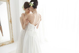 Two brides are hugging each other and the combined amount