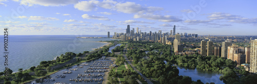 Poster Chicago This shows Lincoln Park, Diversey Harbor with its moored boats, Lake Michigan to the left and the skyline in summer. There is morning light on the city.