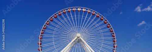 This is an aerial view of the giant Ferris wheel at Navy Pier during summer. It is a view of half the Ferris wheel against a blue sky.