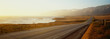 This is Route 1also known as the Pacific Coast Highway. The road is situated next to the ocean with the mountains in the distance. The road goes off into infinity into the sunset.