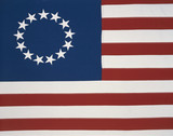 This is the original colonial flag with 13 stars representing the 13 original states at the time of the American Revolutionary War. The 13 stars are against a field of blue and the red and white stripes are sitting flat and move horizontally. - 90028876