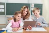 Fototapety lehrerin zeigt kindern etwas am tablet