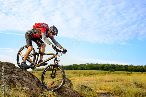 Cyclist Riding the Bike Down Rocky Hill