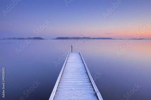 Fototapeta Jetty on a still lake in winter in The Netherlands