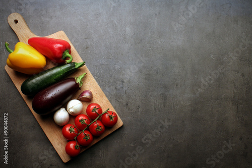 Ratatouille vegetables on wooden cutting board with space for recipe text