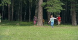 Playful kids hiding behind tree trunks and then running joyfully towards the camera