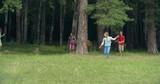 Playful kids hiding behind tree trunks and then running joyfully towards the camera