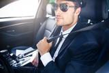 Fototapety Male chauffeur sitting in a car