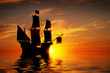 Old ancient pirate ship on peaceful ocean at sunset.