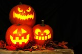 Fototapety Stacked Halloween Jack o Lanterns illuminated at night with old wood and autumn leaves