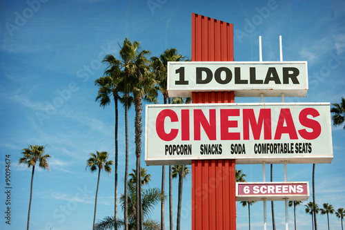 Poster aged and worn vintage photo of cheap dollar cinemas sign with palm trees